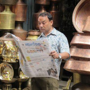 Zeitungsleser in Nepal, umgeben von Klangkörpern: Feuilletonisten schreiben für die Elite der Elite. Foto: Paul-Josef Raue