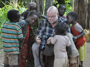 Der Fotograf Thomas Ammerpohl in Äthiopien, von Kindern umringt, denen er seine und ihre Bilder zeigt. Foto: Raue